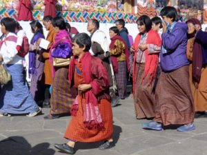 Bhutanese citizens, dressed in festive, brightly colored traditional habits are surrounding a Chorten.