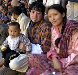 Close-up view on a young and beautiful bhutanese family: a young couple sitting on the floor during a festival with their 1-year-old son glaring friendly and open minded towards the camera. The couple is dressed in the festive brightly colored traditional habits