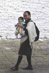 A young man with awakened, smiling eyes behind glasses, with a beart, wearing a black gho and the white scarf for official visits, is walking by the photographer, having his baby on his arm.