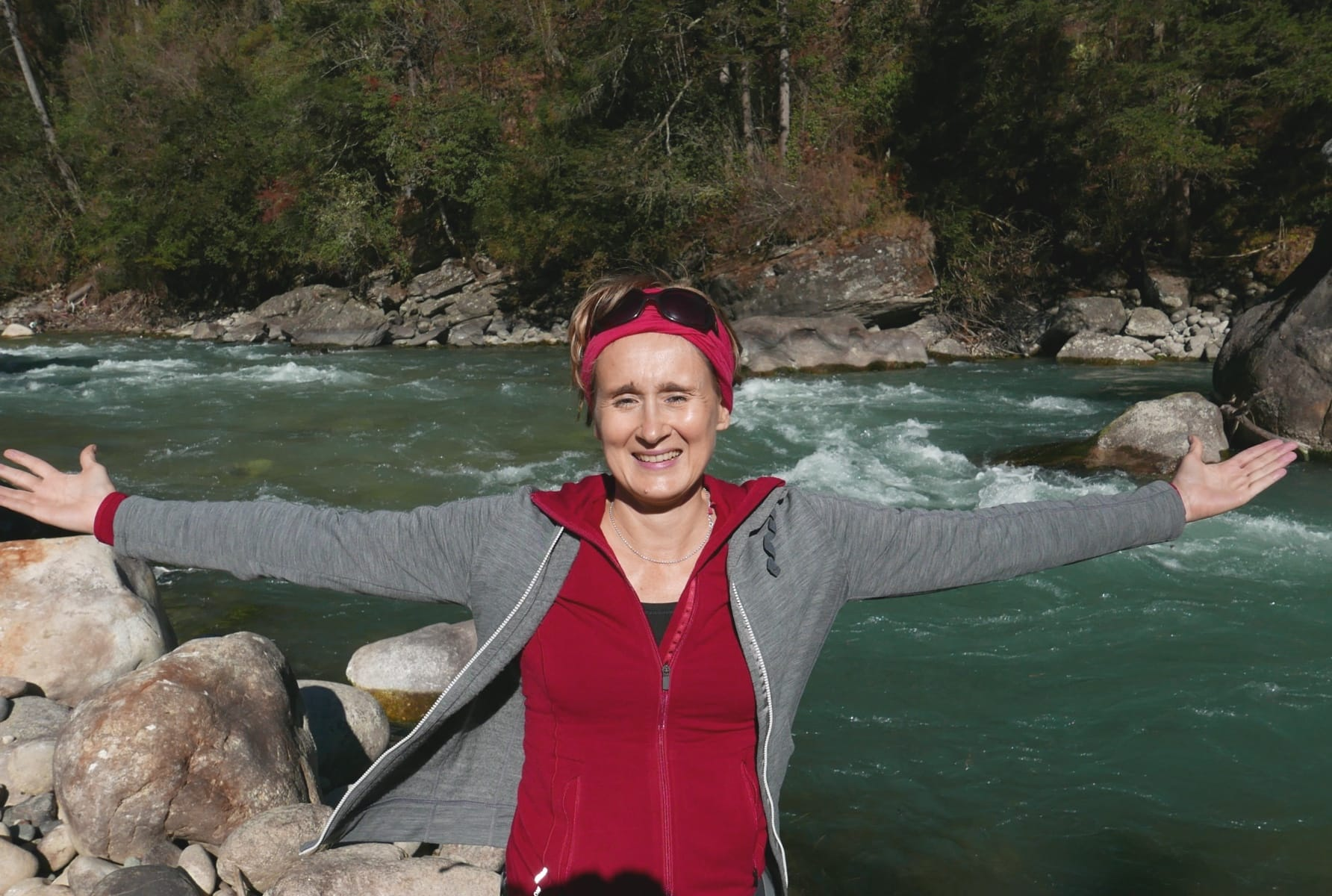 A European woman in red and grey outdoor dress pose in front of the torrential flow of a turquoise colored river. She is spreading her arms to both sides in clear posure of Happiness.