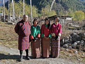 From left to right a huge man in his festive gho and three young woman in brightly colored khiras posing before they start for the visit of a local temple festival