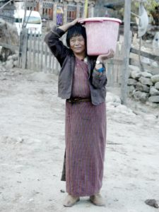 A middle-aged Bhutanese woman pose with a huge plastic bucket on her right shoulder.