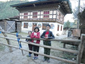 Three kids, two girls and a boy are posing at the gate in front of their family house. The house is framed in the typical timber framed style of Bhutanes architecture, with a basement and one tory.