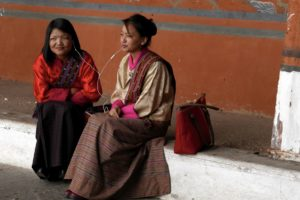 Two girls, approximately in the mid of their 20s sitting on a step in front of a colored red wall inside of a Dzong cortyard. They are dressed in their traditional khiras which look festive or elegant, decorated on their shoulders with a colored scarf. They share an iPhone ear-bud listening to music.