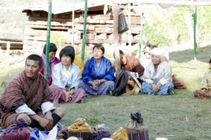 Woman and man in their traditional dress tailor seated on the ground prepared with pine leaves.