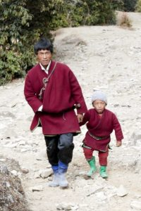 A young man with black hair comes up a mountain together with his son of eventually 5-6 years. They are both dressed in red colored ghos. The man is wearing a sword belt.