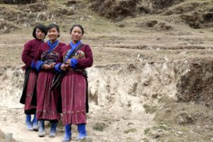 Three girls in natural beautiness with black hair, and rosy cheeks are posing in their traditional red colored dress of the nomad tribes in the Merak-Sakteng region.