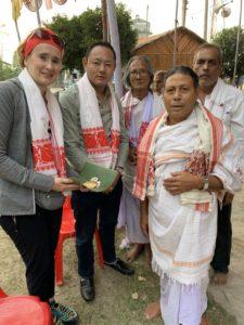 Tshering und werden von einer hinduistischen Gemeinde mit dem weiß-roten Schal begrüßt, der in Assam für ethnische Integration steht, Sahipur, Assam Dezember 2019