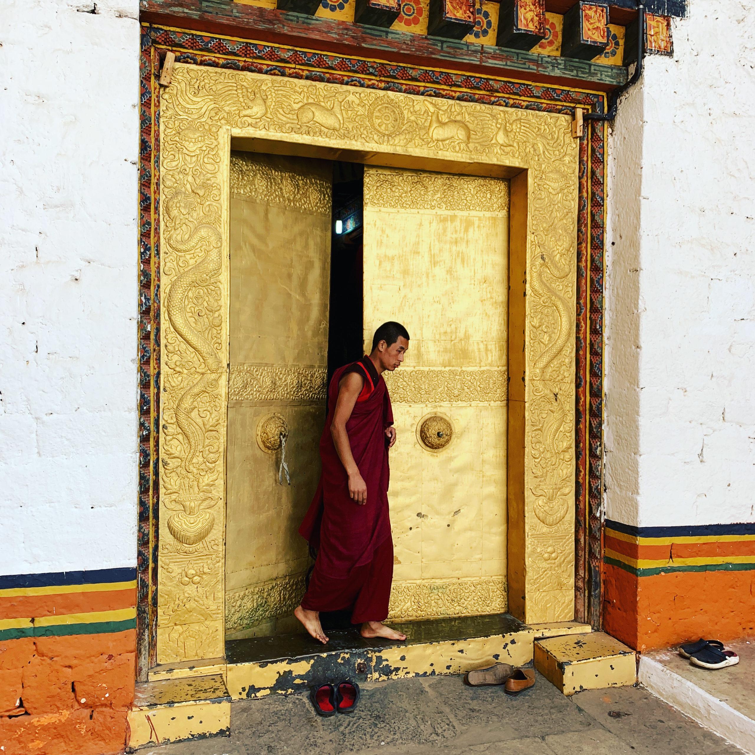 Buddhistischer Mönch tritt aus einem großen, golden bemalten Festungstor