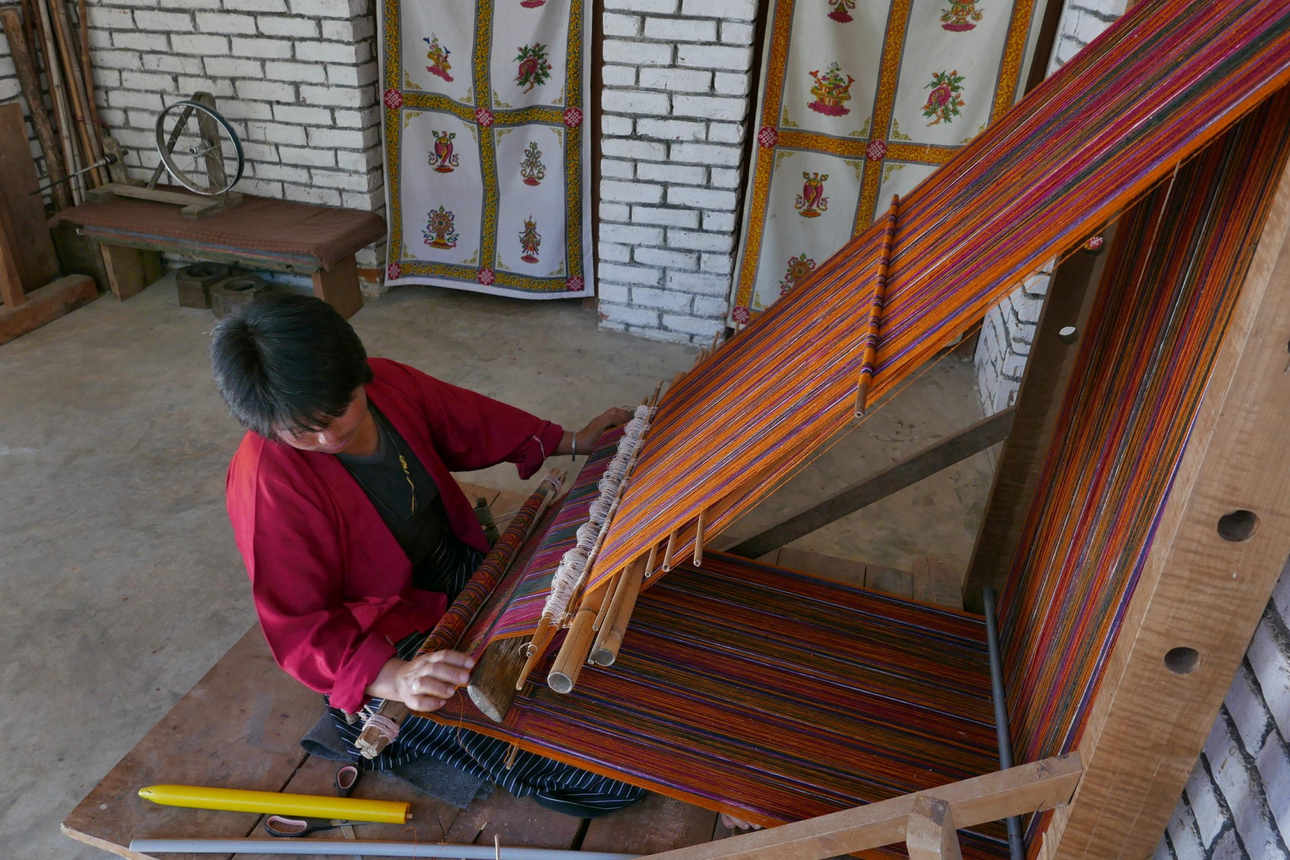 Eine Frau beim Weben an einem flexiblen Webstuhl.