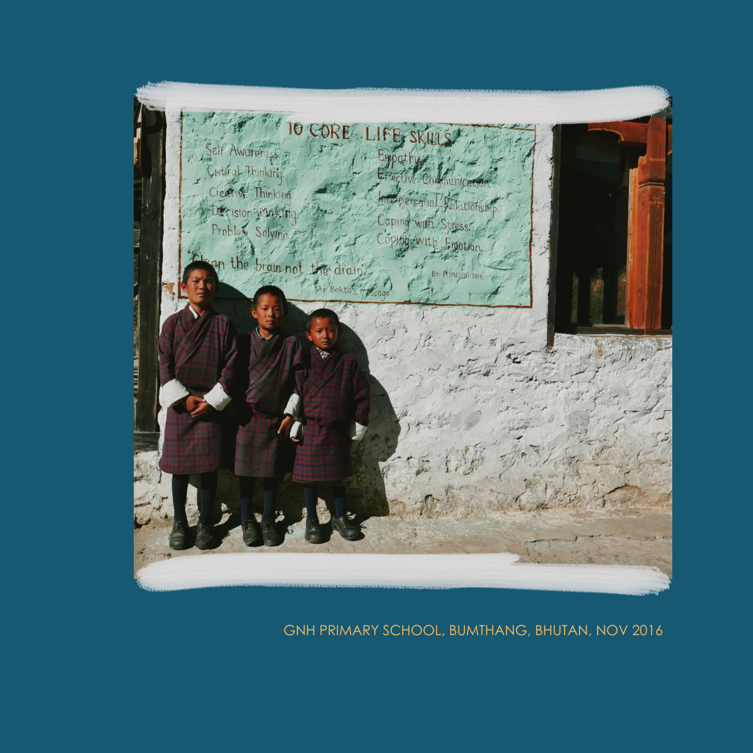 3 Bhutanese school children lined up in front of an outside wall of their school listing ten core skills for life.